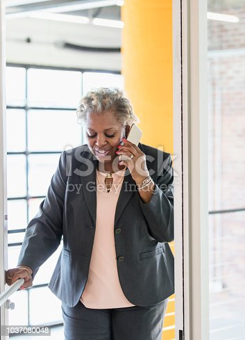 A mature African-American woman in her 50s talking on a mobile phone. She is a businesswoman in an office building, walking through a door.