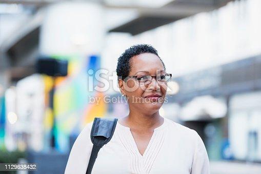 istock Mature African-American woman walking on city street 1129638432