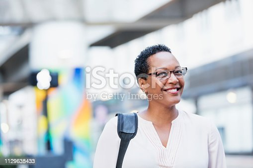 istock Mature African-American woman walking on city street 1129638433