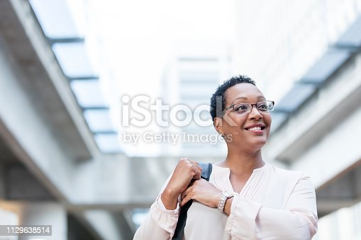 istock Mature African-American woman walking on city street 1129638514
