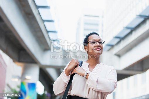 istock Mature African-American woman walking on city street 1144359077