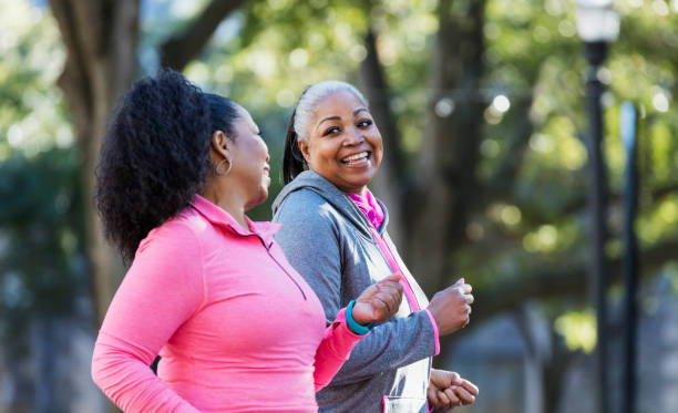 Mature African-American women in city, exercising Two African-American women exercising together in the city, jogging or power walking, laughing and conversing. Buildings and trees are out of focus in the background. The one in pink is in her 60s and her friend is in her 50s. exercising stock pictures, royalty-free photos & images