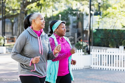 Two mature African-American women exercising together in the city, jogging or power walking, conversing. Buildings and a tree are out of focus in the background. The one in pink is in her 40s and her friend is in her 50s.