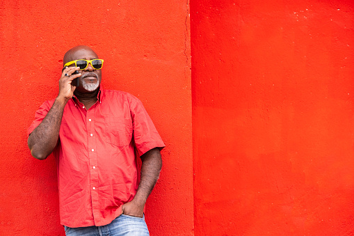 Mature afro man on colorful red background talking on a smartphone