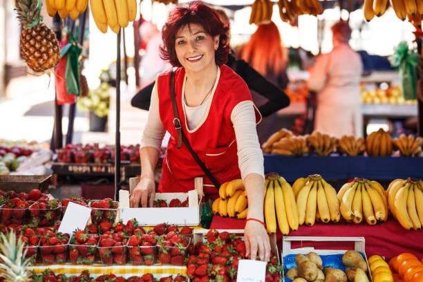 venditore di frutta in età matura selezionando frutta fresca e preparandosi per la giornata lavorativa. - bazar mercato foto e immagini stock