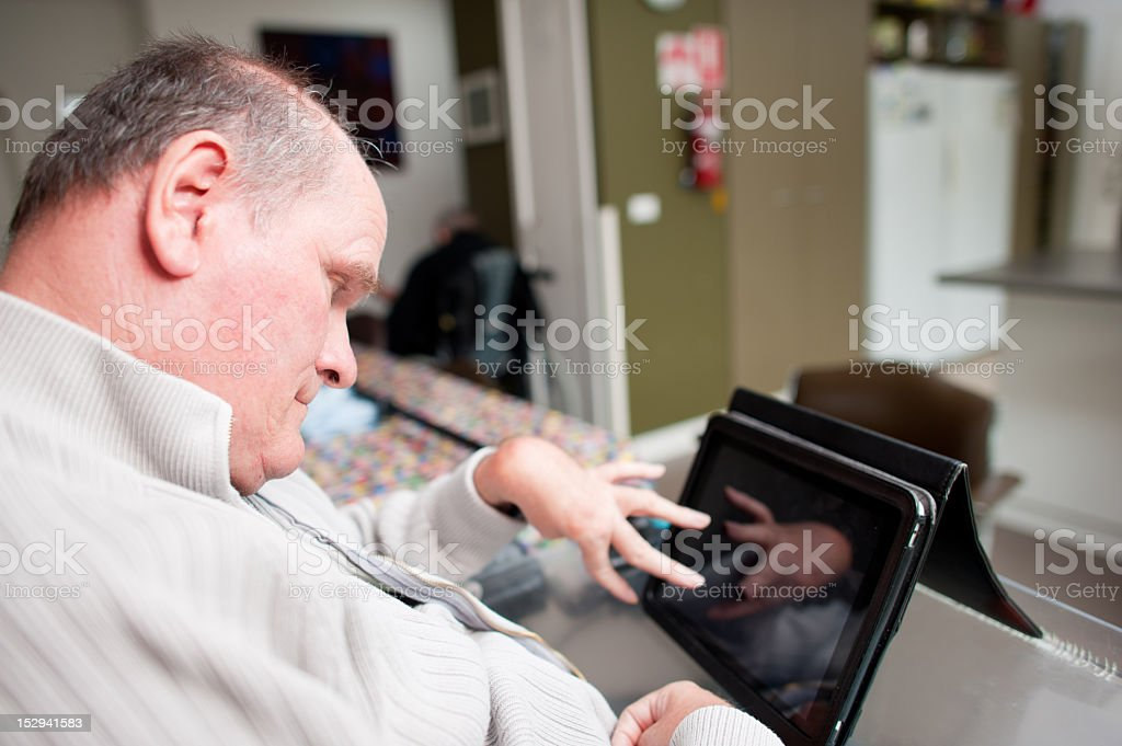 Mature aged man with a disability operating touchscreen computer stock photo