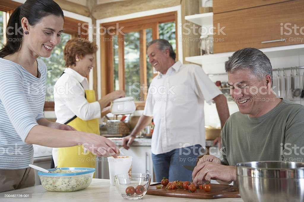 Mature and senior couples preparing food in kitchen royalty-free stock photo