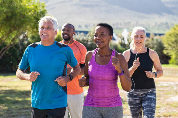 Mature and senior people jogging at park Healthy group of mature people jogging on track at park. Happy senior couple running at park with african friends. Multiethnic middle aged friends exercising together outdoor. active seniors stock pictures, royalty-free photos & images