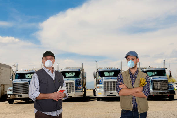 Mature and young truck drivers with protective mask during pandemic