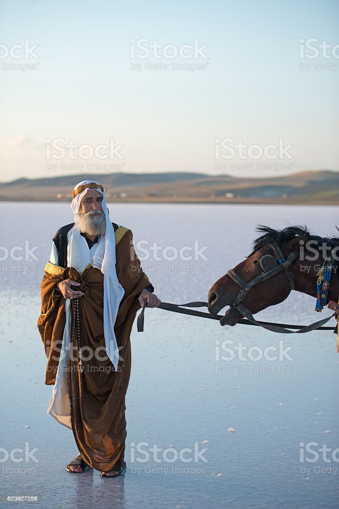 Mature Arabic man with traditional clothes with horse on water stock photo