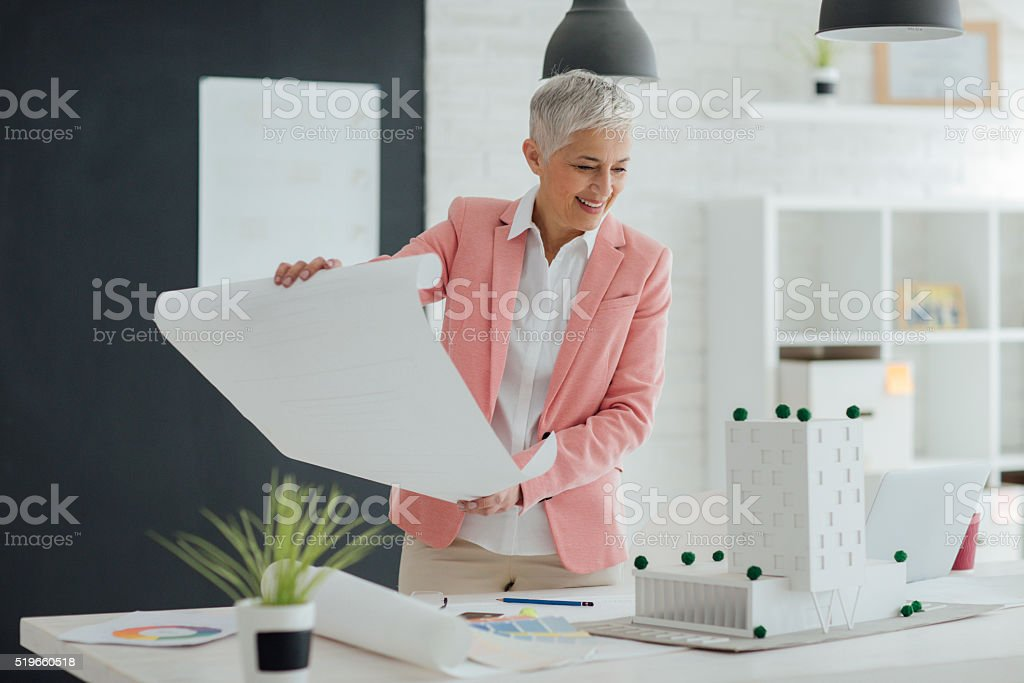 Architect working in her office. Standing , holding blueprint and...