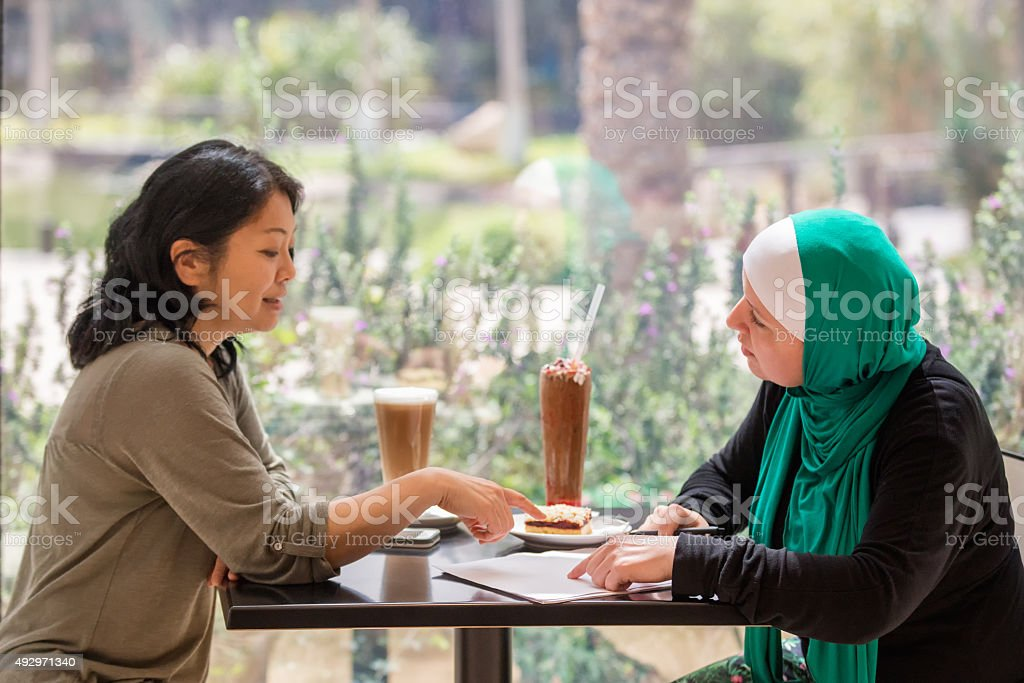 Mature Asian and Middle Eastern Businesswomen Discussing Contract in Café stock photo