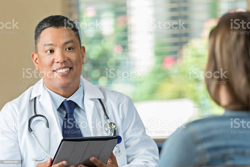 Mature Asian doctor meeting with patient for counseling appointment royalty-free stock photo