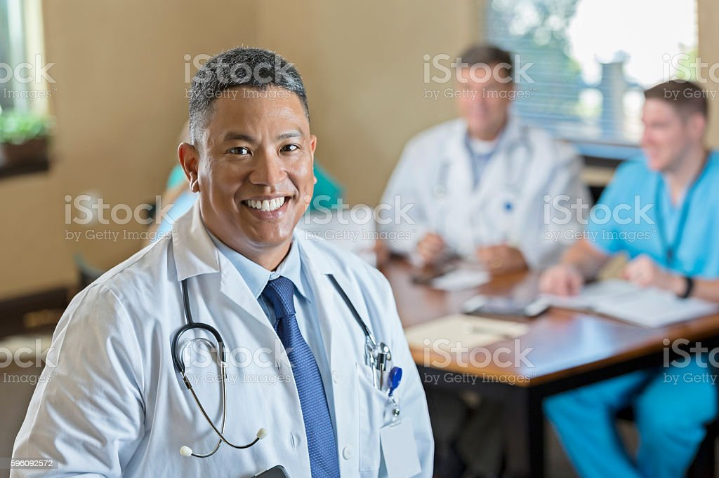 Mature Asian male doctor smiling before hospital staff meeting royalty-free stock photo
