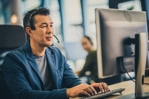 Mature Asian man working in a call center