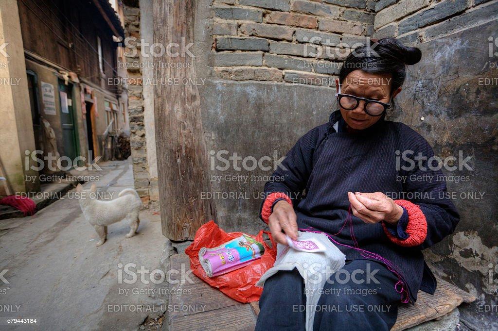 Mature Asian woman embroidery designs on fabric,  Guizhou Province, China. stock photo