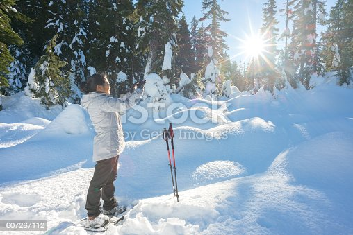 903015102 istock photo Mature Asian Woman Taking Cellphone Photo While Hiking with Snowshoes 607267112