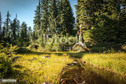 903015102 istock photo Mature, Athletic Asian Man Jumping Over Stream in Alpine Forest 486401564