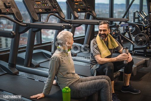 Happy senior couple resting on treadmills in a health club and talking to each other.