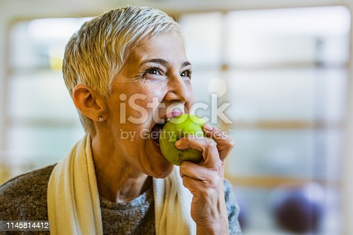 Smiling senior woman biting an apple after sports training in a health club.