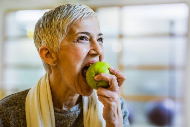 成熟的運動婦女吃蘋果後, 在健身俱樂部鍛煉。 - 咬 個照片及圖片檔