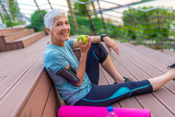 Mature athletic woman eating an apple after sports training Sporty woman eating apple. Beautiful woman with gray hair in the early sixties relaxing after sport training. Healthy Age. Mature athletic woman eating an apple after sports training aging stock pictures, royalty-free photos & images