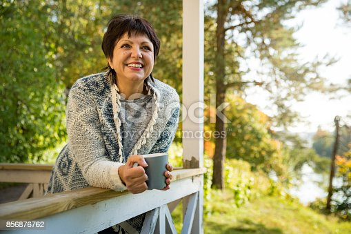 Mature attractive woman standing on terrace with cup of hot coffee wrapped up in knitted warm sweater. Lake house in autumn, yellow and red leaves on trees. Cozy sunny day