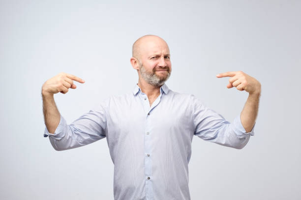 Mature bald adult man with beard standing over grey grunge wall looking confident with smile on face. stock photo