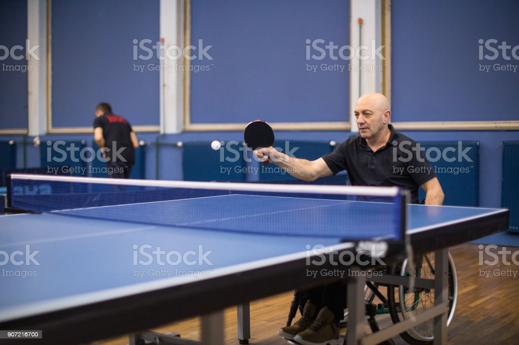 Mature differently abled man in wheelchair playing table tennis...