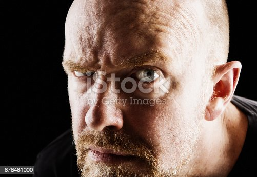 A bearded, mature man frowns, looking anxious and suspicious, against a black background.