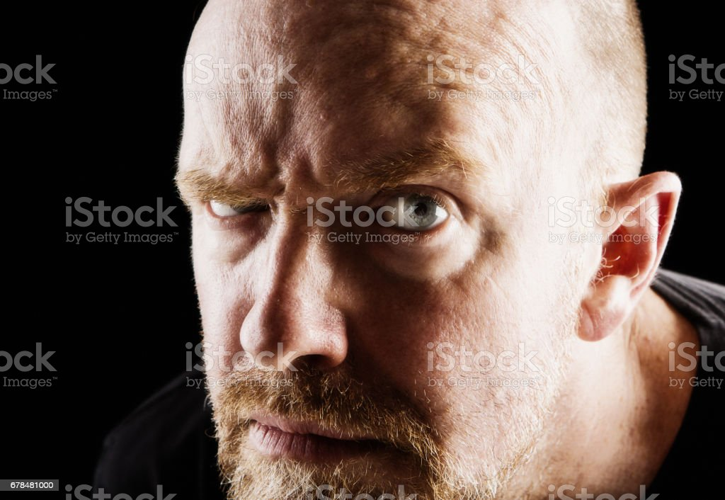 Mature bearded man frowning suspiciously against black background stock photo