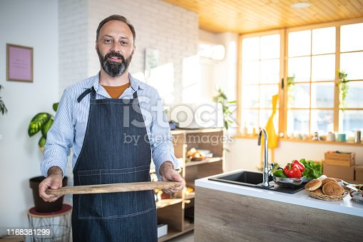 Portrait of Mature bearded man with apron, holding wooden tray in the kitchen, looking at camera