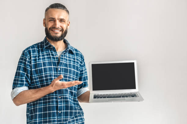 Mature bearded man showing modern laptop with blank screen stock photo