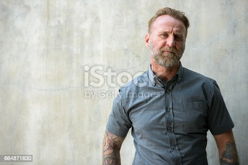 istock Mature bearded man with hand tattoos against urban concrete wall 664871630