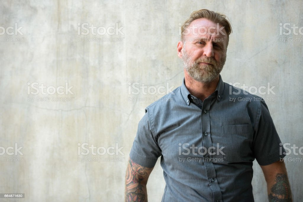 Mature bearded man with hand tattoos against urban concrete wall stock photo