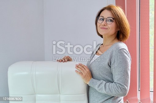 919520858 istock photo Mature beautiful business woman near office leather white armchair 1216587620