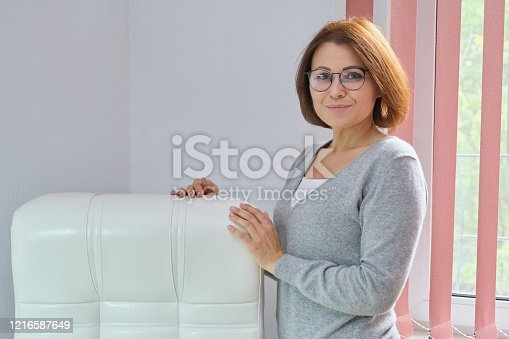919520858 istock photo Mature beautiful business woman near office leather white armchair 1216587649