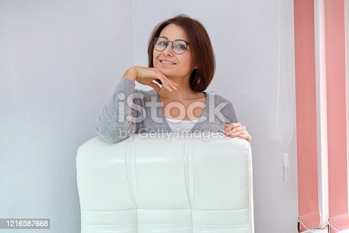 919520858 istock photo Mature beautiful business woman near office leather white armchair 1216587668