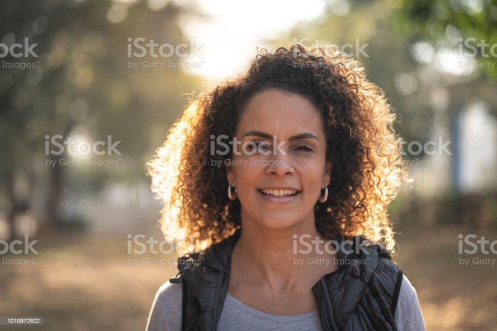 Mujer madura de pelo rizado hermoso mirando a cámara - foto de stock