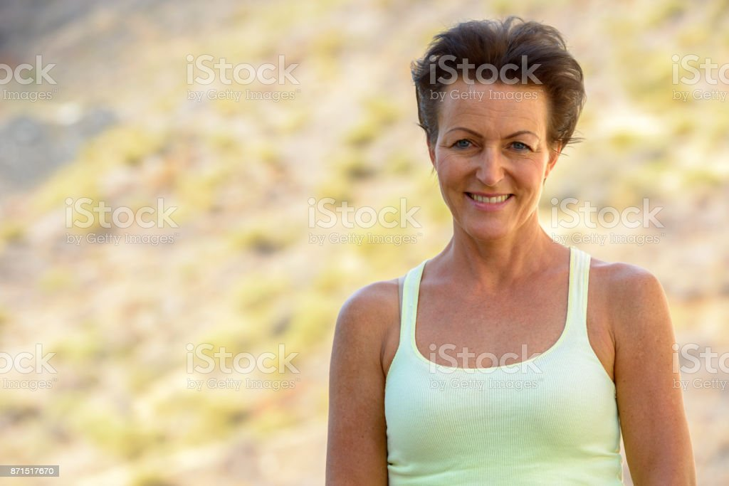 Mature beautiful tourist woman getting away from it all at the beach stock photo
