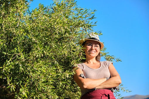 628409126 istock photo Mature beautiful woman in gloves wearing apron hat posing near olive trees 1250057217