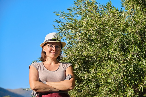 628409126 istock photo Mature beautiful woman in gloves wearing apron hat posing near olive trees 1250057447
