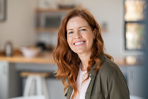 Portrait of smiling mature woman looking at camera with big grin. Successful middle aged woman at home smiling. Beautiful mid adult lady in casual with long red hair enjoying whitening teeth treatment.