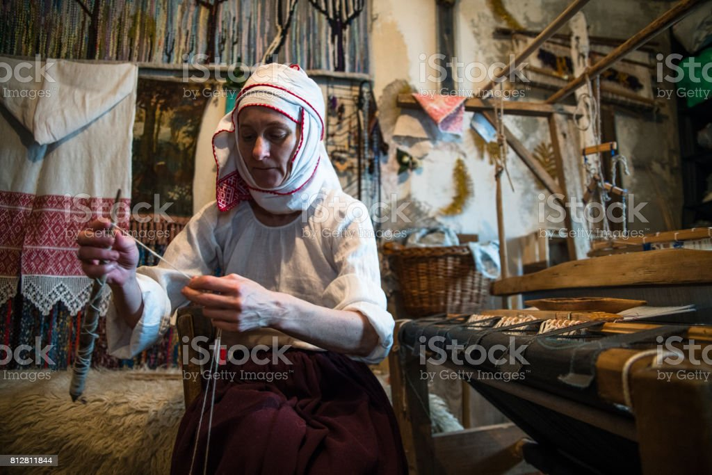 Mature Belarussian woman wearing the traditional dress spinning next to the vintage loom stock photo