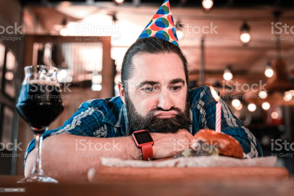 No appetite. Mature birthday man having no appetite looking at his...