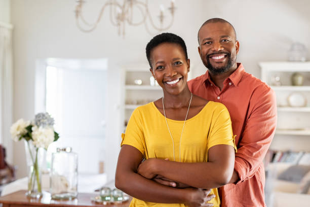Mature black couple hugging and smiling Smiling mature couple holding each other at home. Loving african couple standing in living room embracing and looking at camera. Husband hugging wife from stomach at new apartment with copy space. mature couple stock pictures, royalty-free photos & images