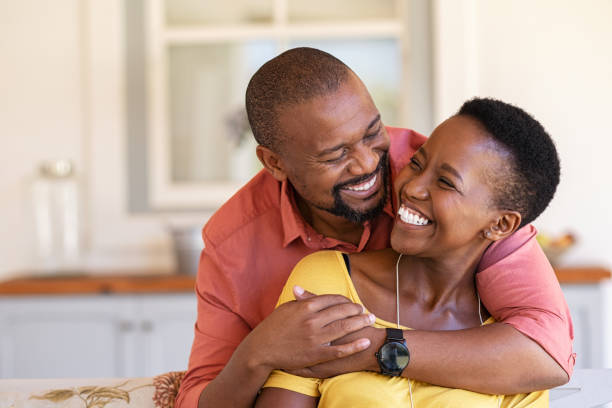Mature black couple in love laughing Mature black couple embracing on sofa while looking to each other. Romantic black man embracing woman from behind while laughing together. Happy african wife and husband loving in perfect harmony. mature couple stock pictures, royalty-free photos & images