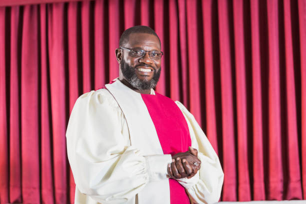 Mature black man in church choir A mature black man wearing robes in a church choir. He is standing in church smiling at the camera, hands clasped in front of him. clergy stock pictures, royalty-free photos & images