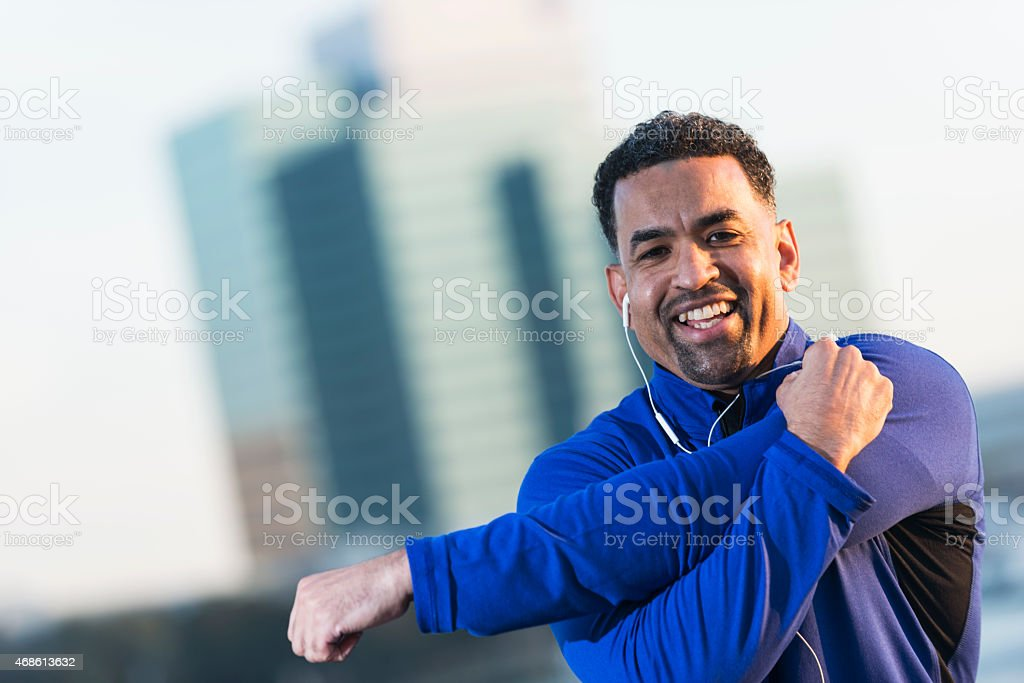 Mature black man in city stretching and exercising stock photo