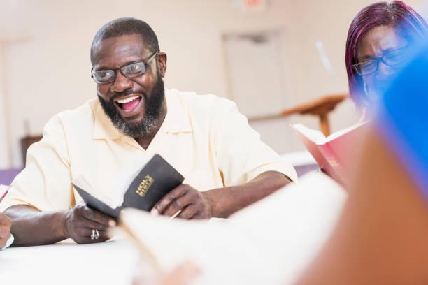 Mature black man speaking in bible study meeting stock photo